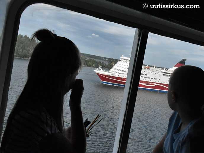 tyttö ja poika tuijottelevat hytiin ikkunasta näkyvää laivaa