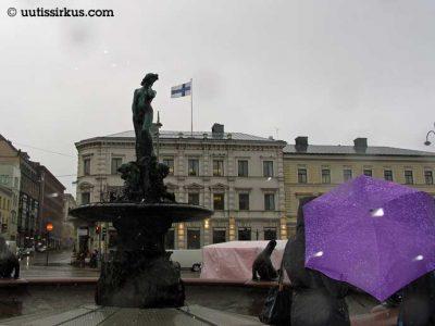 Havis Amanda marraskuussa, sateenvarjoa kantaa joku etualalla, suihkulähteessä ei ole vettä