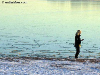 nuori nainen jäätyneen järven rannalla tuijottaa puhelintaan
