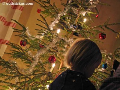 joulukuusen ääressä pieni tyttö selin kameraan