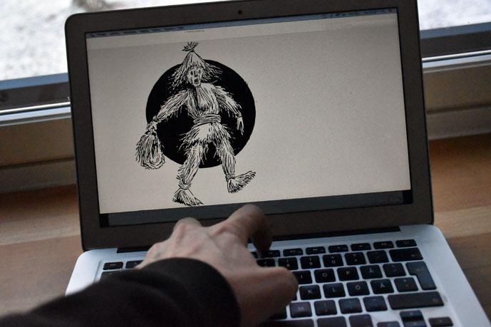 olkiukko-piirros läppärin näytöllä, käsi naputtaa nappuloita