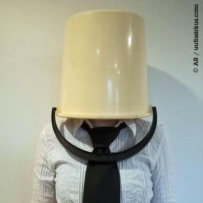 Leveäsolmioinen ihminen ämpäri päässään
