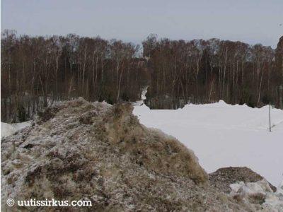 likainen lumikasa pellon reunassa