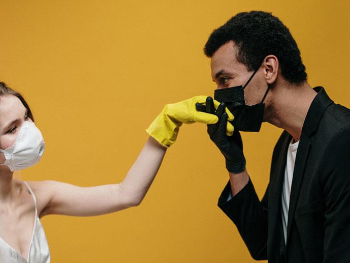 mies hengityssuojain päässään, suojahanska kädessään, suutelee maskiin pukeutuneen naisen kumikäsineeseen verhottua kättä
