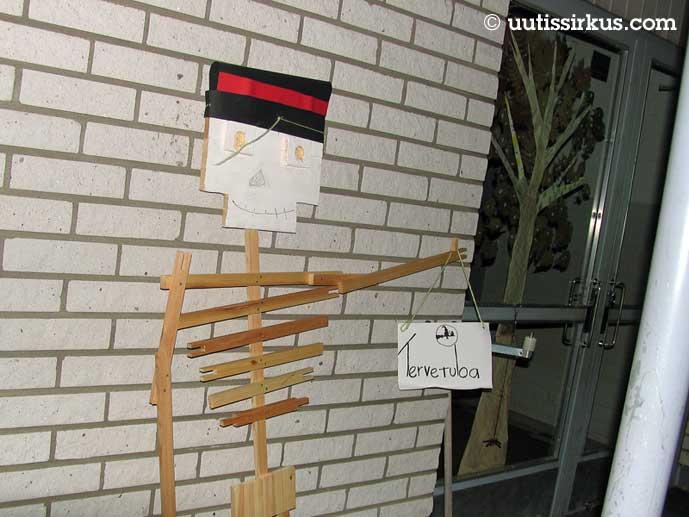 puusäleistä koottu luuranko koulun ovella, kädessä tervetuloa-kyltti