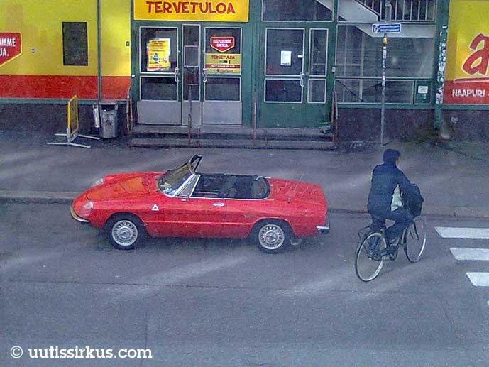 punainen avoauto Alepan edessä, vierestä menee huppupäinen pyöräilijä