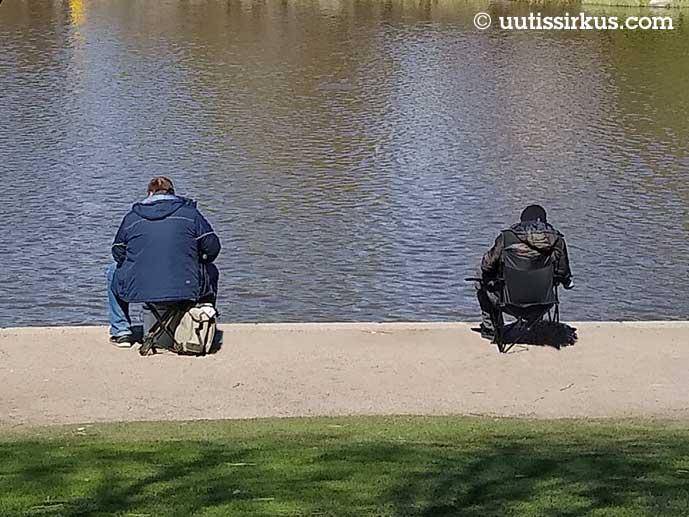 kaksi miestä istuu rannalla, hediän välisensä etäisyys noin kaksi metriä