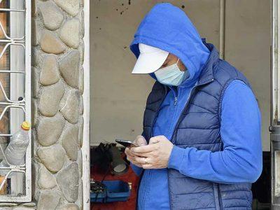 mies räplää puhelintaan maski päässä