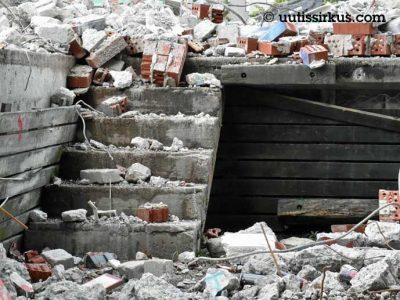 raunioitunut talo: tiilenkappaleita ja betonilohkareita
