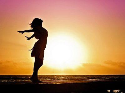 Nainen meren rannalla, aurinko nousee takana merestä