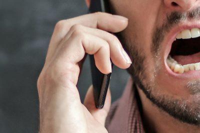 mies suu puolittaisessa irvistyksessä, puhuu älypuhelin korvaallaan