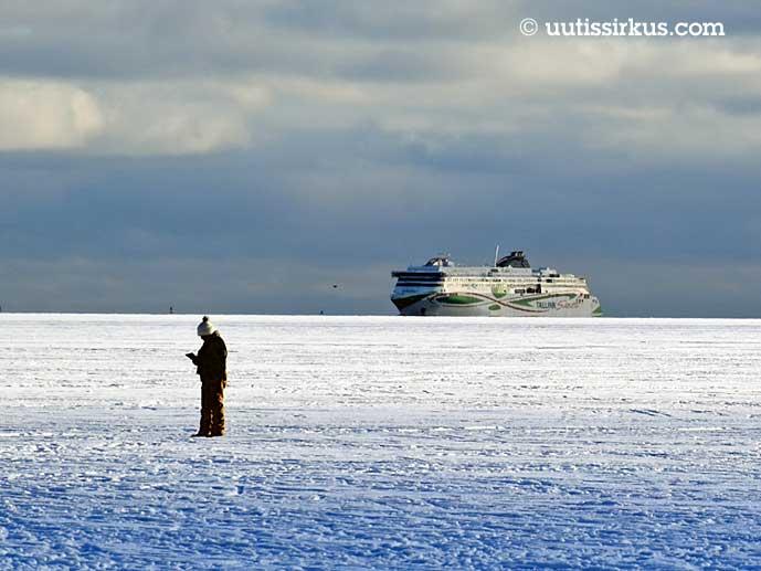 mies katselee puhelintaan meren jäällä, takana näkyy laiva
