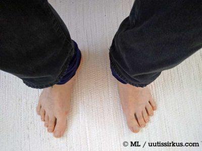 jalassa pitkät housut, varpaat näkyvät valkoisen maton päällä