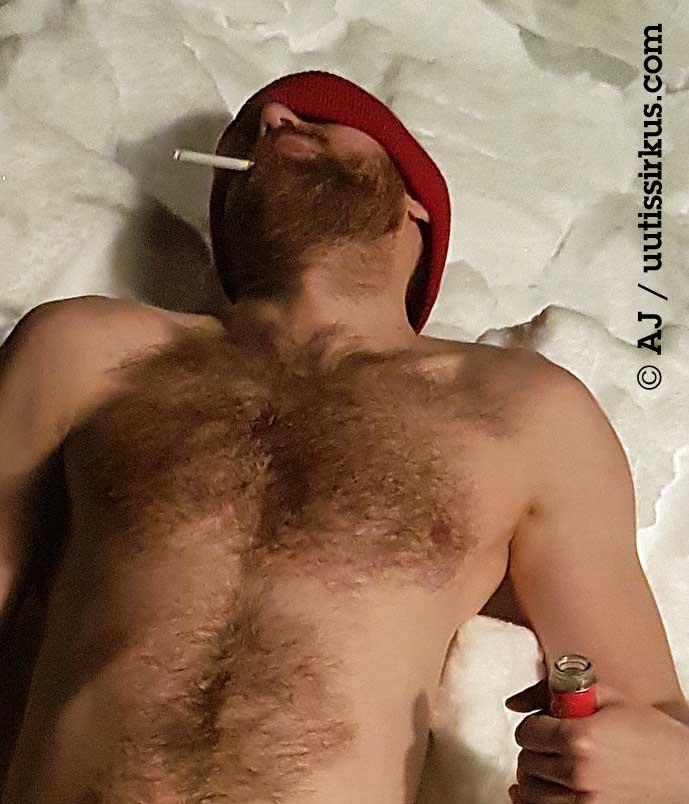 karvainen mies makaa hangessa pipo päässä ilmna paitaa, savuke suussaan
