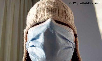 nainen pipo syvällä päässään, maski peittää kasvot, pipo lähes kokonaan silmät