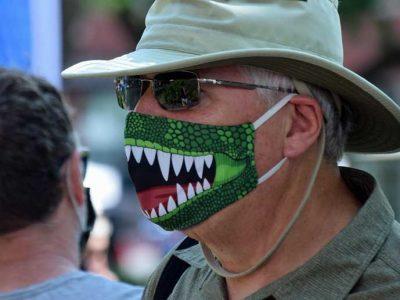 Mies päässään irvistävä maski