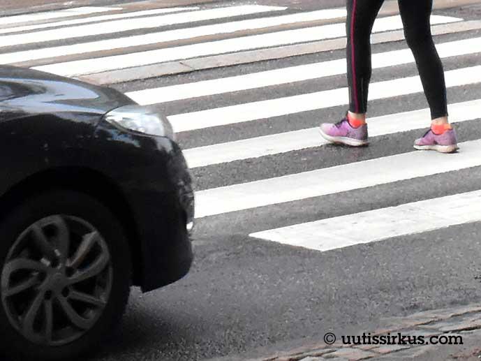 auto on pysätynyt suojatien eteen, yksi ihminen ylittää katua
